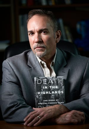 "Keith Saliba, an associate professor of journalism at Jacksonville University, poses with his new book, ""Death in the Highlands: The Siege of Special Forces Camp Plei Me."" It's a true story about U.S. Army Special Forces soldiers besieged by a vastly superior North Vietnamese force in the Vietnam War."