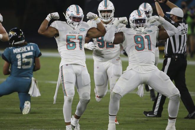 Miami Dolphins outside linebacker Kamu Grugier-Hill and defensive end Emmanuel Ogbah (91) celebrate after sacking Jacksonville Jaguars quarterback Gardner Minshew (15) during the first half of an NFL football game. Stephen Morton/Associated Press