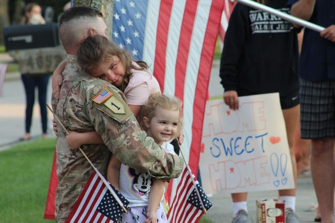 "Sgt. 1st Class Patrick McKelvey surprises his three daughters after serving in the Middle East for 14 months. McKelvey returned to his home in Stow on Friday. Kyrie, 10, hugs her dad while Cora, 6, is behind him and Elsie, 3, gets a hug. The sign sums it up with ""Home, Sweet Home."""