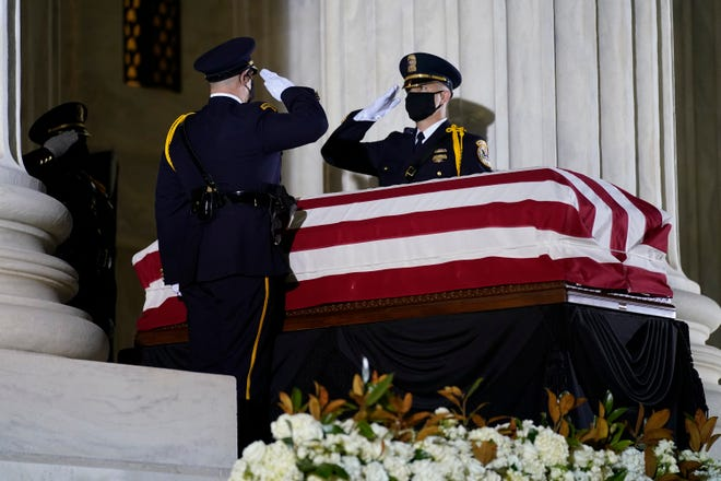 A Supreme Court Honor Guard moves the flag-draped casket of Justice Ruth Bader Ginsburg back into the court as Ginsburg lies in repose under the Portico at the top of the front steps of the U.S. Supreme Court building on Thursday. Ginsburg's death has set up a political showdown between the Republican and Democrat parties as to when an appointment is made to replace her.