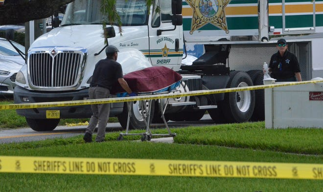 Polk County Sheriff's Office deputies and crime scene investigators transport a body discovered in front of the Mulberry Phosphate Museum on Friday morning just off Hwy. 37 in Mulberry.