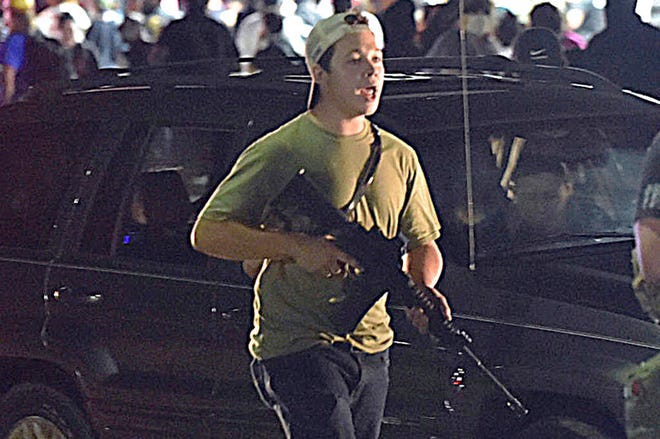 In this Aug. 25 file photo, Kyle Rittenhouse carries a weapon as he walks along Sheridan Road in Kenosha, Wis., during a night of unrest following the weekend police shooting of Jacob Blake. Rittenhouse, a 17-year-old accused of killing two protesters days after Jacob Blake was shot by police in Kenosha, Wisconsin, faces a hearing Friday on whether he should be sent to Wisconsin to stand trial on homicide charges that could put him in prison for life.