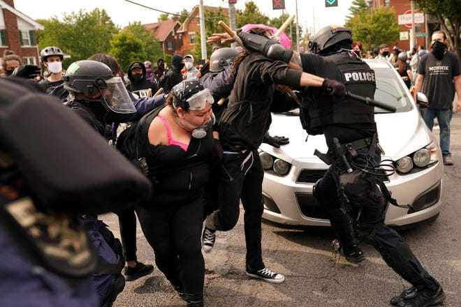 Police and protesters clash during a demonstration over a lack of charges against Louisville police in Breonna Taylor's death Wednesday in Louisville, Ky.