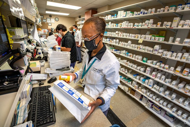 Lori Gainous, pharmacy manager at Central Florida Health Care, fills a prescription order at the clinic. Leaders of the nonprofit say insurance and drug companies are undermining a federal program that allows the provider to sell medications to patients at deep discounts.