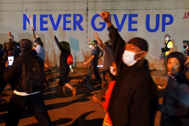 Protesters march, Thursday in Louisville, Ky. Authorities pleaded for calm while activists vowed to fight on Thursday in Kentucky's largest city, where a gunman wounded two police officers during anguished protests following the decision not to charge officers for killing Breonna Taylor.