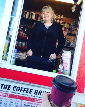 Suzzanne Mendenhall, owner of The Coffee Brake, hands a customer coffee. The business recently celebrated 20 years in business in Mount Shasta.
