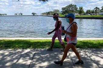 "Eva Johnson (left) and Liz Cillo walk along the waterfront in St. Petersburg on Wednesday. Trump recently said that COVID-19 was seriously affecting ""virtually nobody"" under the age of 18 and sought to frame the pandemic as largely impacting older Americans, as he argued for school districts to resume in-person learning.  ""We're dispensable. We're old,"" Cillo said. ""I feel as though he's never showed any empathy or compassion toward us."""