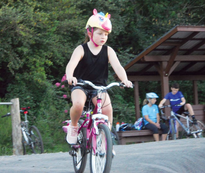A young cyclist rides the pumptrack at the Dirtlab while other people sit underneath the nearby gazebo.