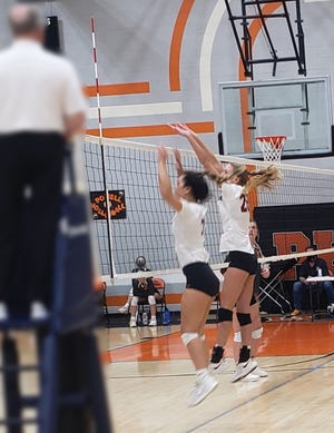 Oak Ridge's Lynley Baldwin and Brenna Allred, both seniors, go up for a block against the Panthers at Powell High School.