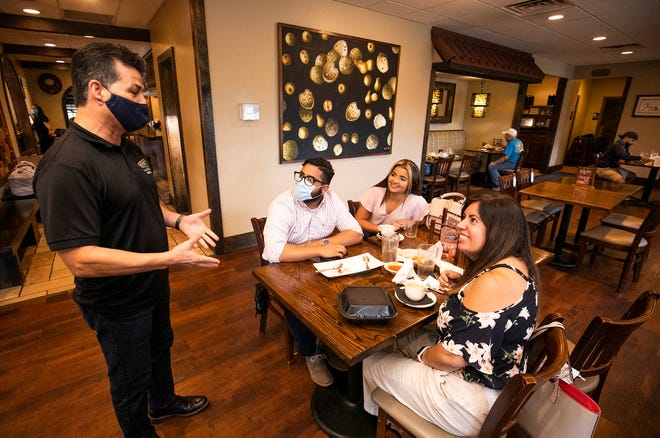 Webster Luzuriaga, owner of Latinos Y Mas, talks to a table of diners at the restaurant on Friday afternoon. While Florida Gov. Ron DeSantis announced on Friday that restaurants can open at 100% capacity, some local restaurants, including Luzuriaga's, will stay at 50% seating for the time being.