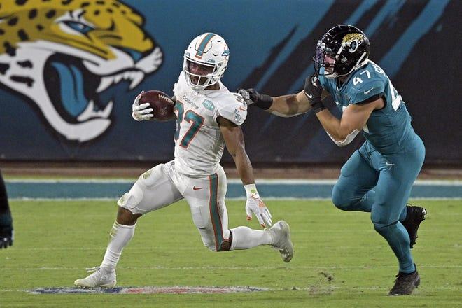 Dolphins running back Myles Gaskin eludes Jaguars linebacker Joe Schobert.