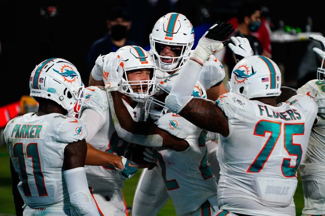 Miami Dolphins tight end Mike Gesicki (88) celebrates with teammates after scoring a touchdown against the Jacksonville Jaguars during the second half at TIAA Bank Field.