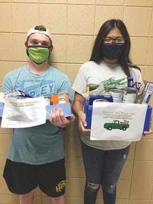 Andrew Van Slyke, junior class secretary (left) and Liz Adame, PHS student council member-at-large  are finding food collection boxes full as they check on participants in the 2020 Drive to Thrive effort to serve the community.