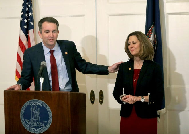 Gov. Ralph S. Northam, left, gestures toward his wife, Pamela, during a press conference in February 2019 at the Executive Mansion in Richmond, Va.