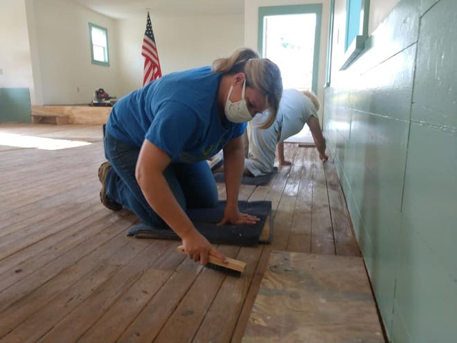 Freedom Township Fiscal Officer Jennifer Derthick cleans the floors during a work day at Freedom's one-room schoolhouse.
