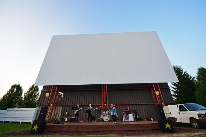 Members of the LRB Band perform on stage in front of the screen at the Midway Drive In.