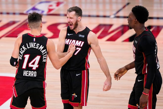 Miami's Tyler Herro (14), Goran Dragic, center, and Bam Adebayo celebrate the Heat's 112-109 win over Boston on Wednesday in Game 4 of the Eastern Conference finals. The Heat can wrap up the series and a berth in the NBA Finals with a win Friday night.