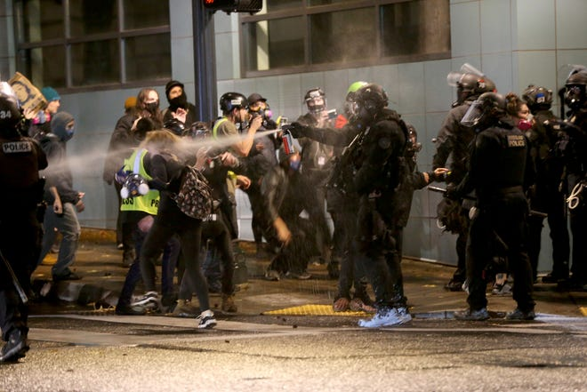Protesters demanding the end of police violence against Black people are sprayed by police during a demonstration in Portland on Wednesday.