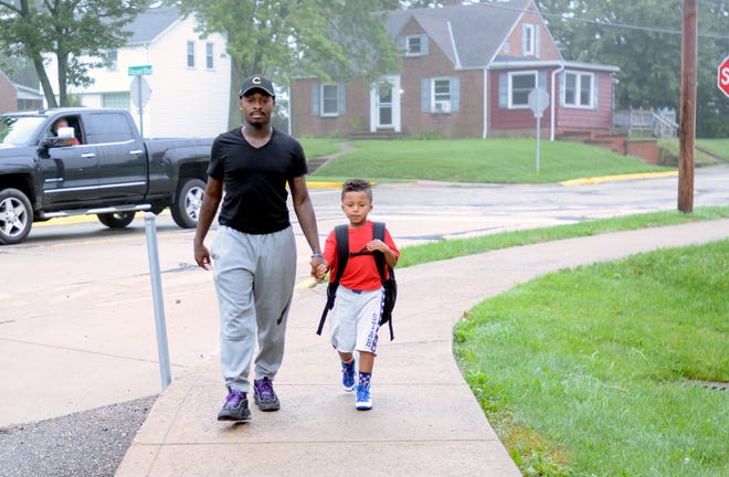 In this file photo, Lance Willis holds the hand of his son, Xzavion Willis, 6, as they walk to Parkway Elementary School in observance of Fathers Walk their Kids to School.