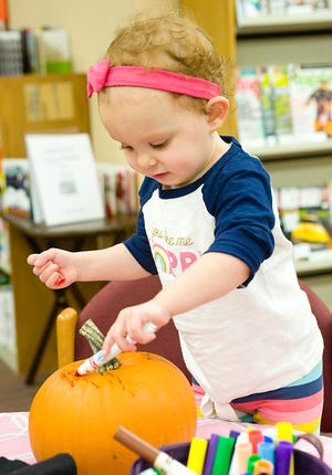 Marlow James, 1 1/2, draws on a pumpkin during a make-and-take pumpkin decorating event on Oct. 2018 at the Rodman Public Library in this file photo. (Michael Skolosh, Special to the Alliance Review)