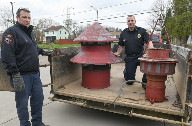 Canton Township Fire Chief Christopher Smith (left) is leaving his post for a job in Alaska. He's seen here at the former Sherman Church SW fire station on April 16 as East Sparta Fire Department Captain Zach Adams (right) picks up an emergency warning siren. (CantonRep.com / Ray Stewart)