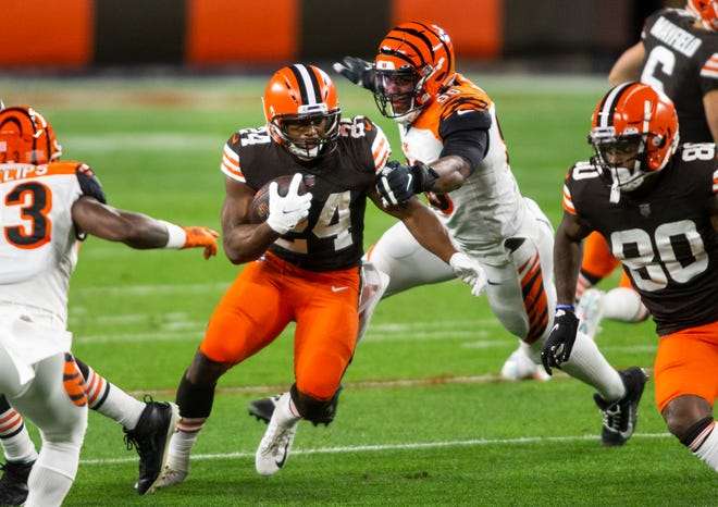 Sep 17, 2020; Cleveland, Ohio, USA; Cleveland Browns running back Nick Chubb (24) runs the ball past Cincinnati Bengals defensive end Carlos Dunlap (96) during the first quarter at FirstEnergy Stadium. Mandatory Credit: Scott Galvin-USA TODAY Sports