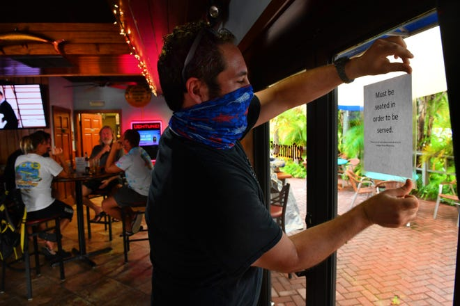 Michael Donaldson, manager at West End Pub in Gulf Gate, posts a sign on a door to the bar's outdoor seating.