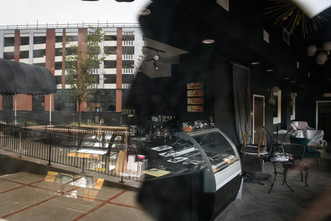 The parking deck on Hay Street is reflected in the window of the new Coffee Scene, a coffee shop on the first floor of the Prince Charles Hotel. The coffee shop opening, which is planned for later this year, was held up because of COVID-19. [Andrew Craft/The Fayetteville Observer]