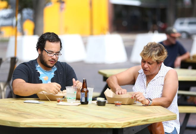 Wilkins Delgado eats with his mother Ana Ortiz at one of the outdoor dining tables in downtown Gainesville outside Loosey's on Friday. Gov. Ron DeSantis has moved the state into Phase 3, allowing restaurants to operate without capacity restrictions based on the coronavirus pandemic.