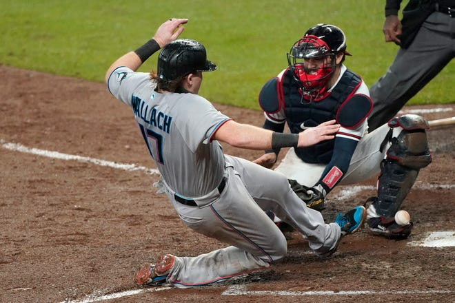 Miami's Chad Wallach scores on a Jon Berti double as the ball gets away from Atlanta catcher Travis d'Arnaud during the sixth inning Thursday.
