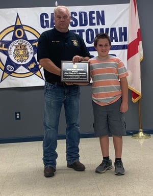 Ron Leek, president of Gadsden/Etowah FOP Lodge No. 2, presents a Hero Award to J.C. Hutchins of Southside, a 9-year-old whose fast action is credited with saving the life of his younger brother this summer.