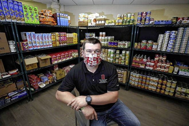 Nick Fowler, Buckeye Food Alliance coordinator, sits inside the pantry in Lincoln Tower on the Ohio State University campus. The Tri-Village Lions Club and other Ohio Lions Club chapters have made 1,400 masks they plan to either donate to the pantry, or sell to raise money for it.