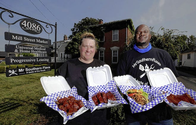 Renee Glover and her husband, Neal Newsome, display items available at their new restaurant, MrSouthernflava, 4068 Broadway in Grove City's Town Center. Meals include, from left, jumbo wings with house sauce, baby-back ribs with Hennessy sauce, the Big Mouth burger and St. Louis-style ribs with Kick'n sauce.