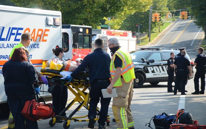 First responders take a man to the ambulance after he was injured on Goguac Street near Capital Avenue Southwest on Friday.  Trace Christenson/The Enquirer