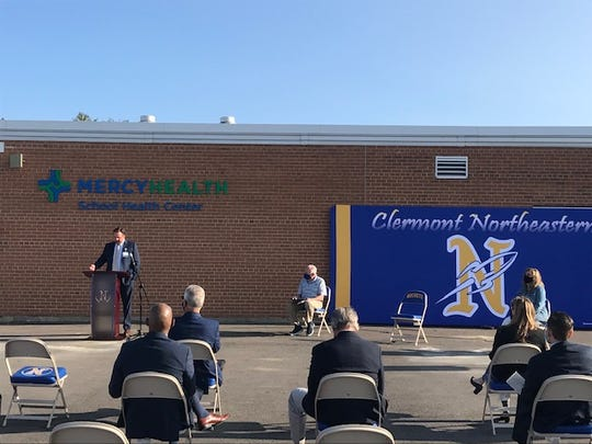 Shane Knisley, president of Mercy Health - Clermont Hospital, speaks to a socially distanced audience at a recent ribbon-cutting ceremony for the new health center at Clermont Northeastern High School.