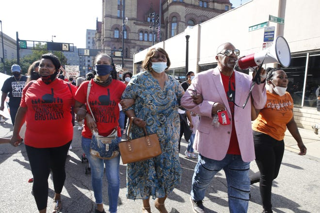 Audrey DuBose, center, marches with Bishop Jerome McCarry during the Ohio Families Unite Against Police Brutality march through Downtown on Friday. DuBose's son, Sam DuBose, was unarmed when he was shot and killed by white former University of Cincinnati Police Officer Ray Tensing during a 2015 traffic stop.