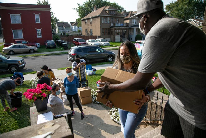 Larry Charleston hands Mayra Perez a box of food Sept. 24. Both are members of Brilliant Detroit, a group that makes weekly donations to families in need.