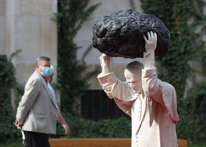 Seorang pengunjung Museum Nasional berjalan melewati patung baru mendiang paus, St. Yohanes Paulus II.