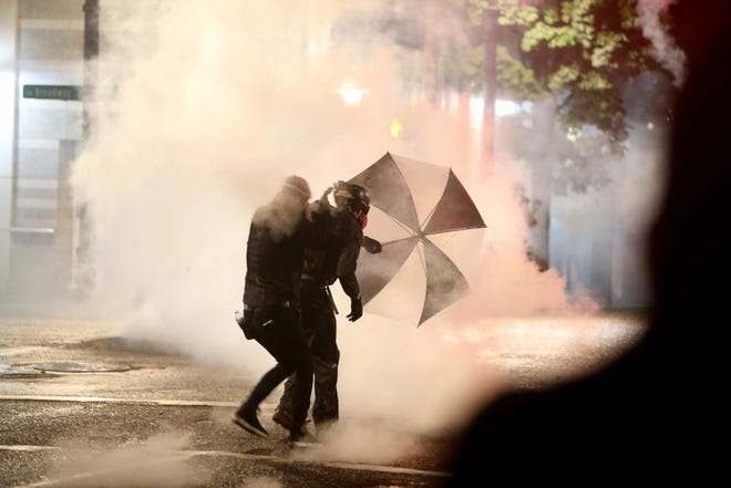 Protesters demanding the end of police violence against Black people take cover from smoke during a demonstration in Portland, Ore., on Wednesday, Sept. 23, 2020.