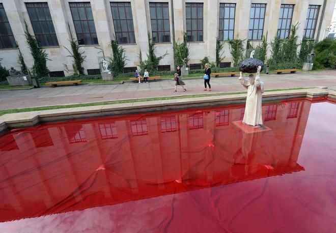 """Pengunjung Museum Nasional berhenti di depan patung baru mendiang paus, St. Yohanes Paulus II, yang melemparkan batu ke a """"Diracuni dengan Baik""""."""