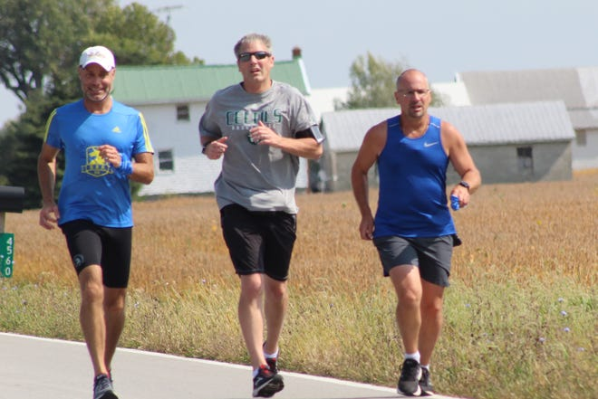 Dave Slater, pictured left, Jason Hawkins and Jeff Jackson run together during their leg of the Great American Relay Thursday in Sandusky County. A group of eight runners took part in the national relay, which started Sept. 15 and runs through Oct. 21, stretching from Boston to Los Angeles.