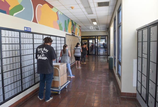 Customers line up while following social distancing guidelines at the U.S. Postal Service's Tamuning location on Sept. 25, 2020.