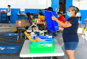 Agana Heights Elementary School one-to-one school aide Rena Tayama sanitizes a bin used to exchange resource learning material at the school in this Sept. 25 file photo. Public schools still want to drop the hard-copy learning option, according to Superintendent Jon Fernandez.