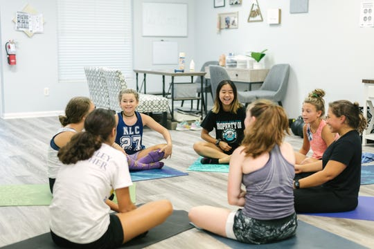 Participants in the Wellfit Girls programming sit in a circle.