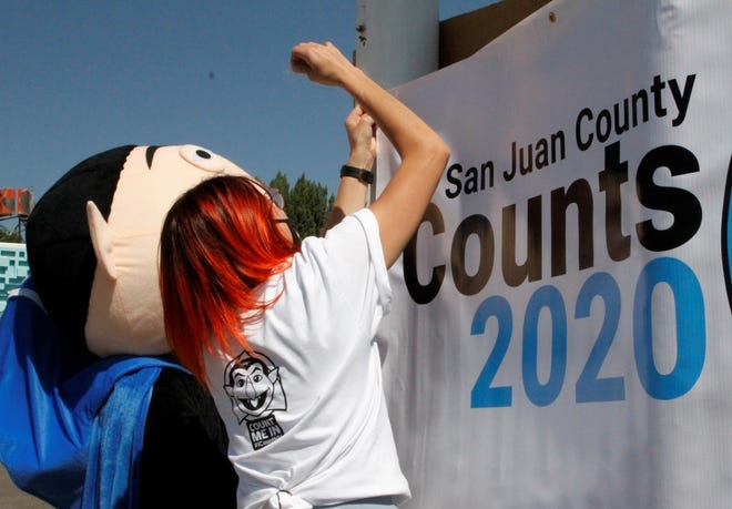 Shelby Markle and Levi Thomas hang up a sign encouraging people to fill out their 2020 Census.