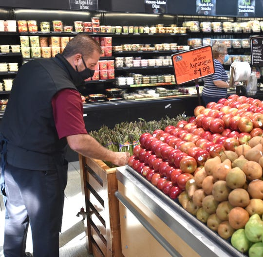 Joe's Produce employee Kais Zaya freshens up their fruit and vegetable display on Sept. 25, 2020.