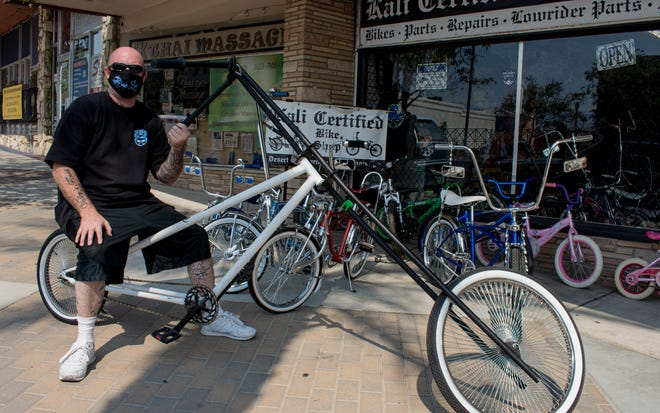 Casey Lather, one of the owners of Kali Certified Bike Shop in Desert Hot Springs, Calif., sits on his custom made chopper bicycle on September 18, 2020