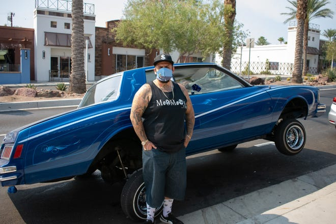 Mr. MooMoo, one of the owners of Kali Certified Bike Shop, poses in front of his car in Desert Hot Springs, Calif. on September 18, 2020.
