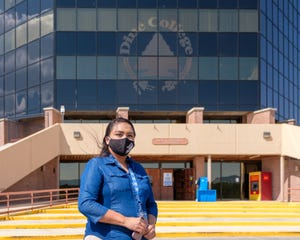 Jazzmine Martinez, marketing assistant, poses with her mask outside the Ned Hatathlie Center at the Tsaile campus of Diné College.