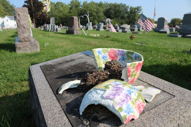 A broken ceramic vase sits atop a tombstone at the Lakeview Cemetery in Port Clinton. Items like these will be removed and disposed of next week as part of the seasonal cleanup.